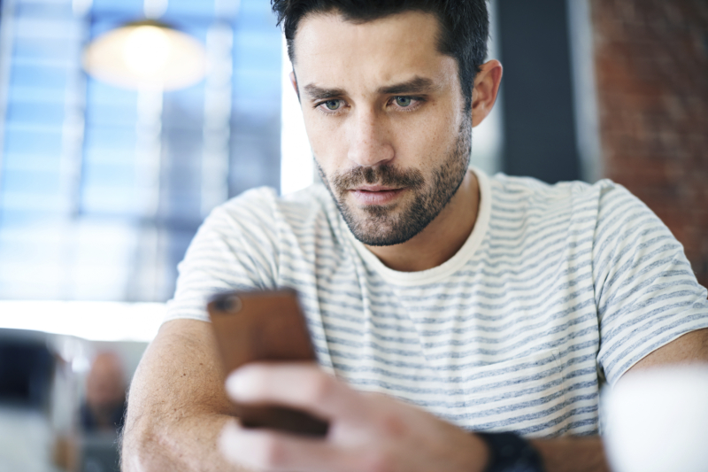 Shot of a handsome young man using his mobile phone while sitting at a restaurant table