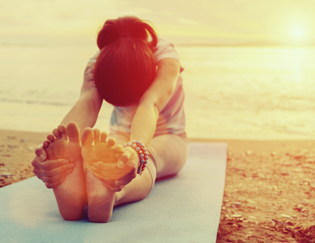 Young woman doing yoga exercise on summer beach at sunset. Image with sunlight effect