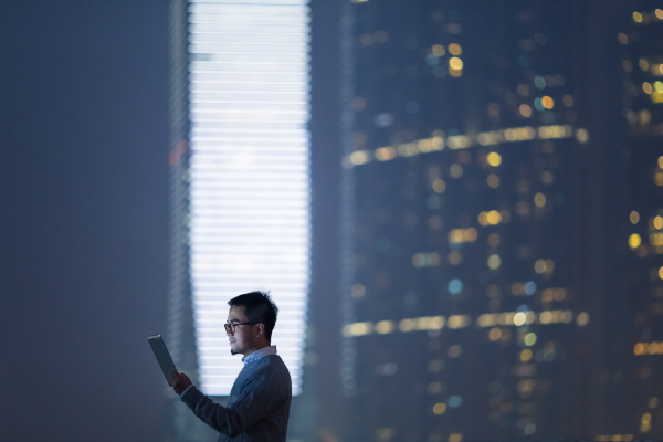 Smart businessman using and looking at digital tablet in city, standing against illuminated financial skyscrapers at night time.