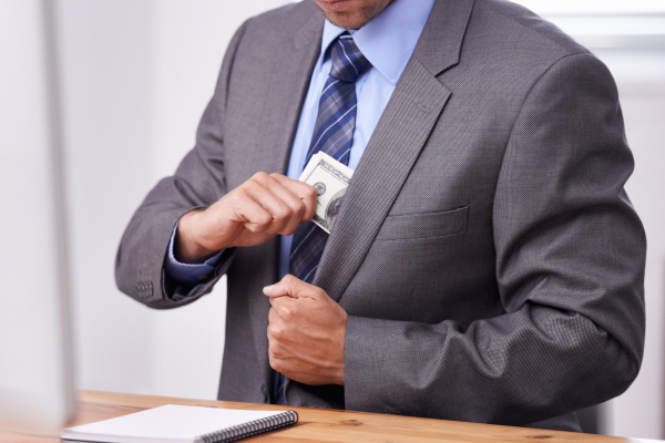 Cropped shot of a businessman putting money into his blazer pocket