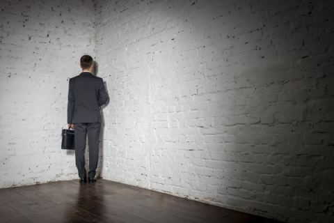 Businessman standing in corner of a room