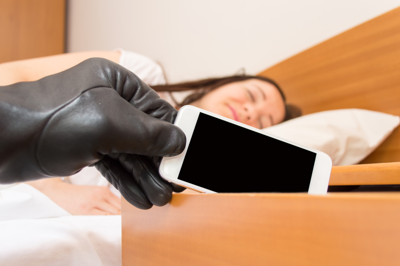 robber steals the smartphone of the nightstand while woman sleeps deeply