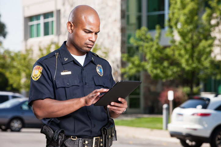 A mid-adult male african american law enforcement officer uses a modern electronic touch screen tablet to enter a citiation or look up information while outdoors.