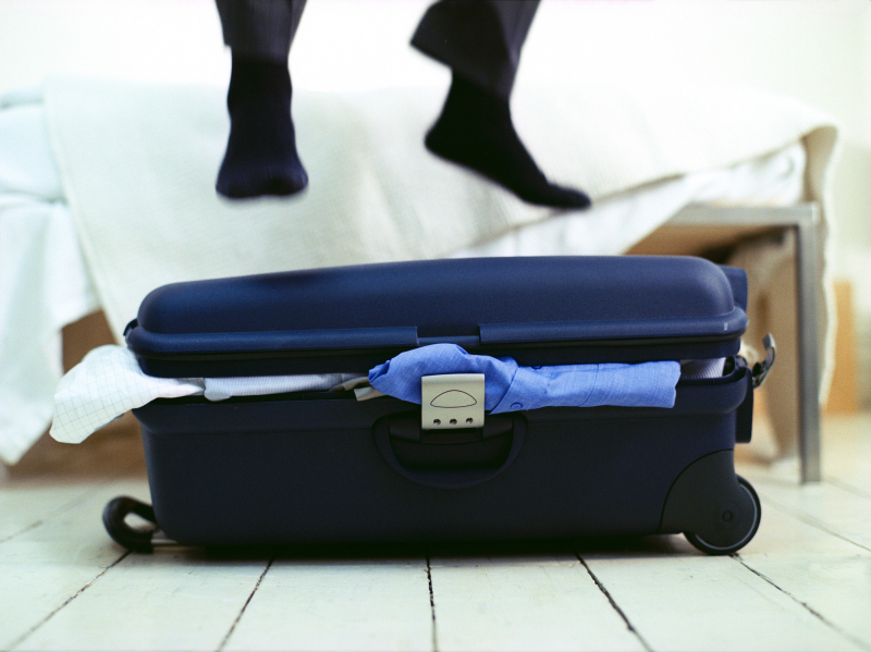 Businessman jumping on overflowing suitcase in bedroom, low section