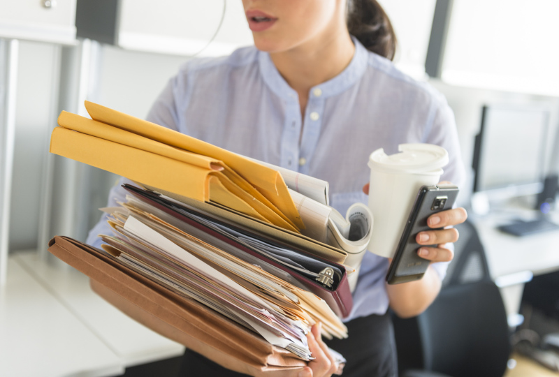 USA, New Jersey, Jersey City, Business woman holding stack of documents in office
