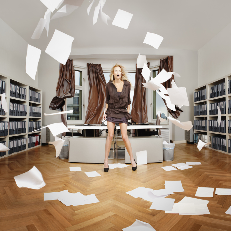 A woman standing in an office while sheets of paper blow around the room