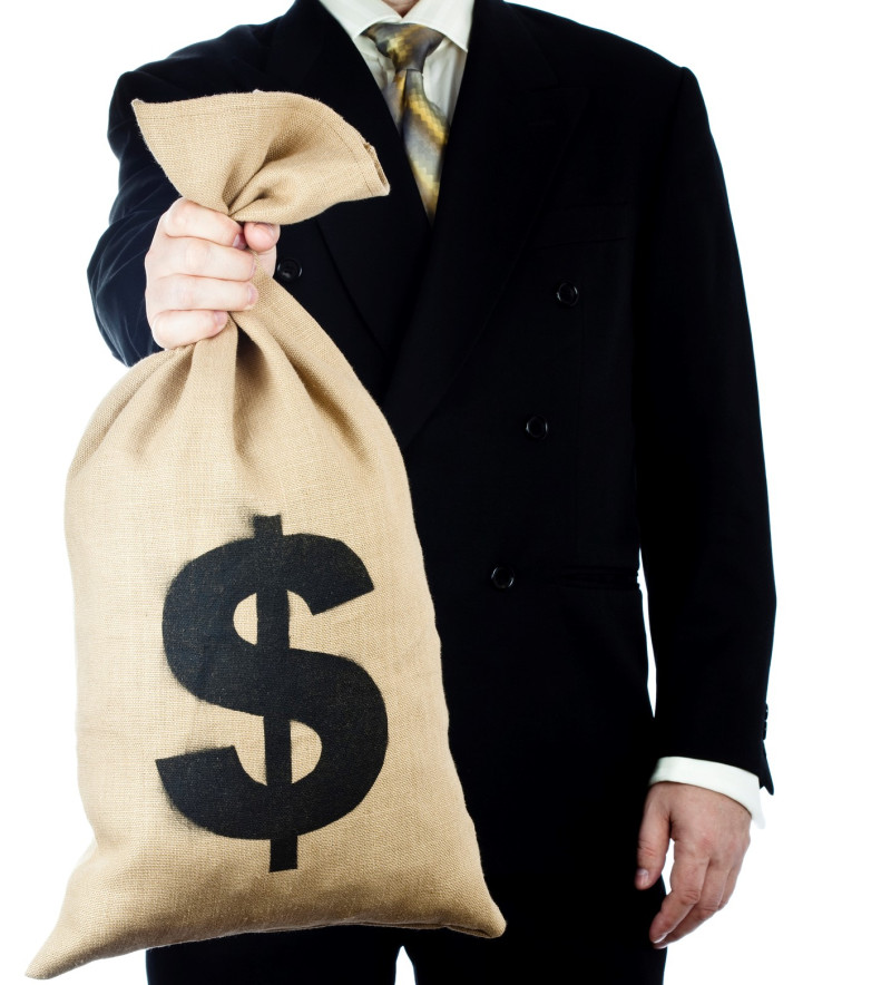 Businessman holding a bag full of money. Isolated on white.